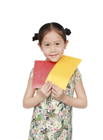 Portrait of happy little Asian girl wearing cheongsam smiling and holding gold and red envelope. Happy Chinese New Year.