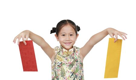 Happy little Asian girl wearing cheongsam smiling and holding gold and red envelope over white background. Happy Chinese New Year.