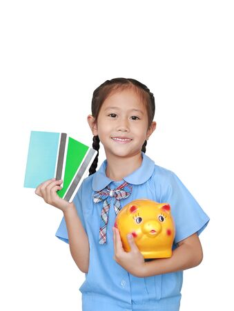 Portrait of happy Asian little girl in school uniform holding account book and piggy bank isolated over white background. Schoolgirl with bank passbook. Money saving concept.