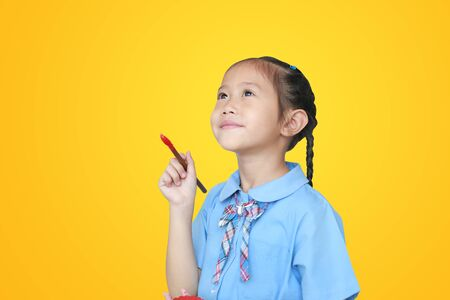 Asian little schoolgirl in school uniform holding Red dipped paintbrush thinking of drawing something over yellow background.