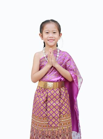 Beautiful Asian kid girl in traditional thai dress praying isolated on white background. (Sawasdee is meaning hello). Фото со стока
