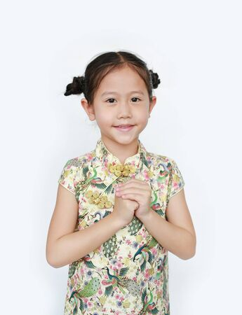Beautiful Asian little girl in traditional cheongsam with greeting gesture celebration for happy Chinese New Year over white background. Фото со стока