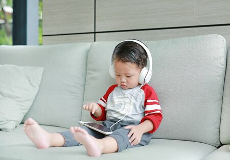 Adorable little Asian baby boy in headphones is using a smartphone lying on the sofa at home. Child listening to music on earphones. Фото со стока