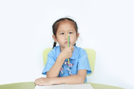 Little girl in school uniform hold and looking pencil in her hand over white background focus at pencil. Kid girl with thinking something while studying.