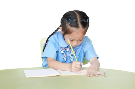 Intend little kid girl in school uniform writing on notebook at desk isolated over white background. Фото со стока