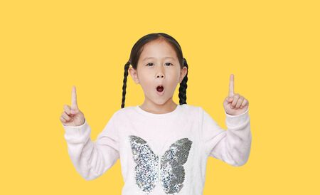 Excited little kid girl pointing two forefinger up isolated over yellow background.
