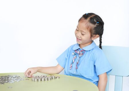 Cheerful Asian little girl in school uniform sitting on table with stack of coins for saving over white background. Kid counting money. Schoolgirl with Money saving for the future concept.