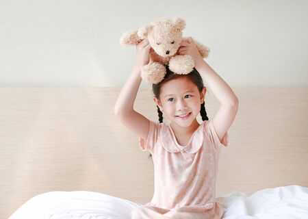 Smiling Asian little girl showing teddy bears while sitting on the bed at home. Фото со стока