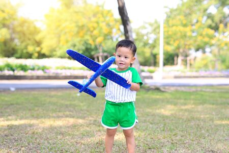 Adorable little baby boy age about 2 year old playing a toy plane in the garden. Фото со стока