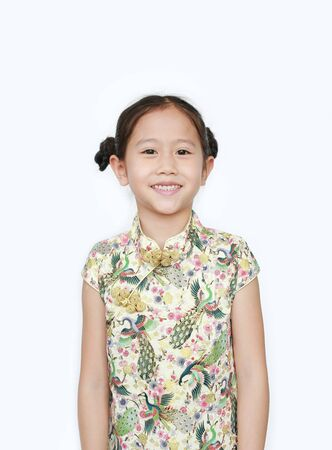 Portrait of happy little Asian girl wearing cheongsam with smiling over white background. Happy Chinese New Year. Фото со стока