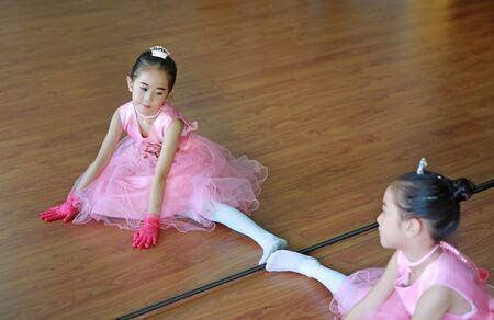 Cute little ballerina girl in a pink tutu doing exercises on the floor with mirror reflection.