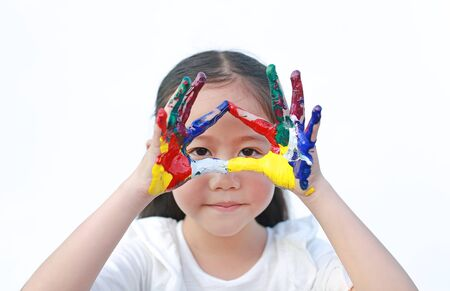 Adorable little girl looking through her triangle colorful hands painted over white background.