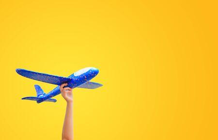 Mano de niño de primer plano levantar un avión de juguete azul volando aislado sobre fondo amarillo con espacio de copia.