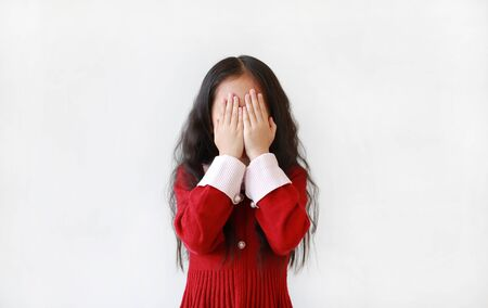 Little Asian child girl covering eyes with hands isolated over white background. Фото со стока