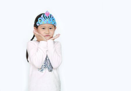 Portrait of smiling little Asian kid girl with wearing a crown toys isolated over white background.
