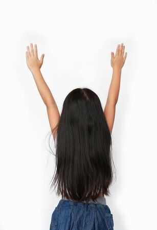 Little Asian child girl raising hands up isolated over white background. Rear view.