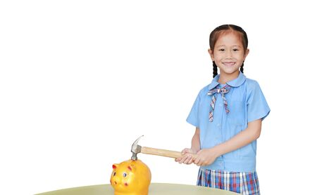 Happy little asian girl in school uniform preparing to break the piggy bank with a hammer on white background at table. Schoolgirl with Money saving concept.