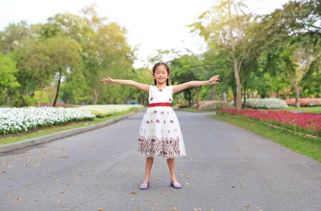 Portrait of happy little girl closed eyes and open wide her arms standing on road in the garden. Фото со стока