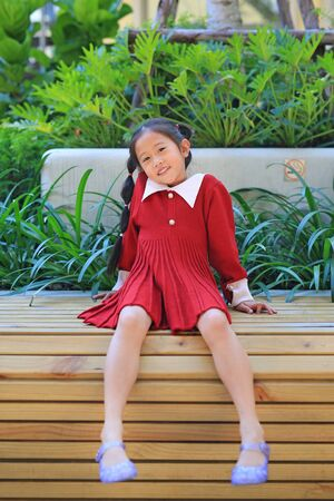 Happy Asian little girl in red dress sitting and lying on wood bench in the garden.