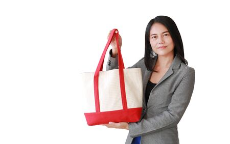 Asian woman holding a cotton fabric bag isolated over white background. Eco friendly bag for reduce or zero waste concept. Фото со стока