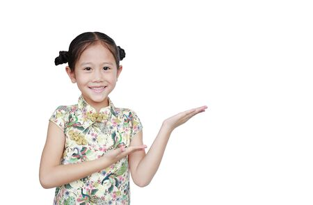 Happy Asian little girl wearing cheongsam with smiling and greeting gesture celebrating for happy Chinese New Year isolated on white background with copy space for your text.