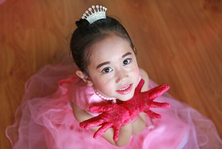 Beautiful little Asian ballerina girl in a pink tutu expression hands open. Фото со стока
