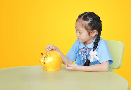 Portrait of Asian little girl in school uniform sitting on table and putting coin into piggy bank isolated on yellow background. Schoolgirl with Money saving concept. Фото со стока
