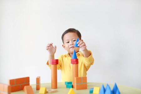 Cheerful little baby boy playing a colorful wood block toy on table over white background.