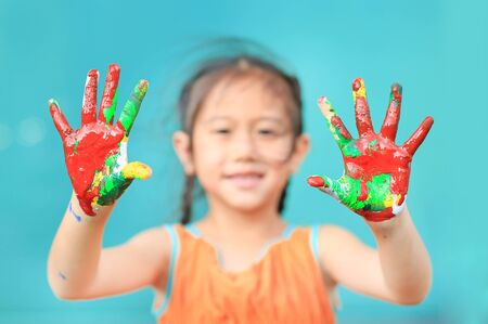 Portrait of smiling little girl looking through her colorful hands painted. Focus at baby hands.
