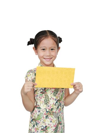 Happy Asian little girl in traditional cheongsam with holding gold envelope for happy Chinese New Year isolated on white background. Фото со стока