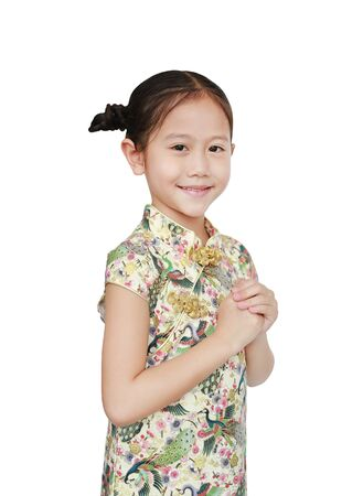 Beautiful Asian little girl in traditional cheongsam with greeting gesture celebration for happy Chinese New Year over white background Фото со стока