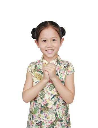 Asian little girl in chinese traditional dress with greeting gesture celebrating for happy Chinese New Year. Фото со стока