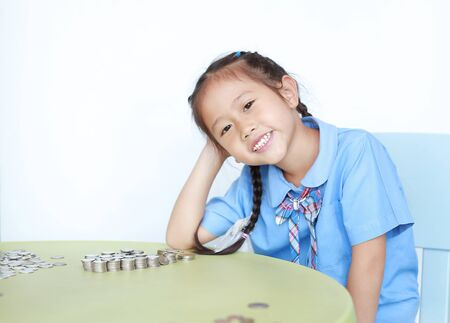 Smiling Asian little girl in school uniform sitting on table with pile of coins for saving over white background. Kid counting money. Schoolgirl with Money saving for the future concept.