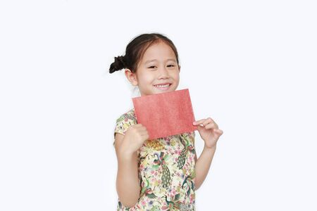 Happy little Asian girl wearing cheongsam smiling and holding red envelope isolated on white background. Happy Chinese New Year. Фото со стока