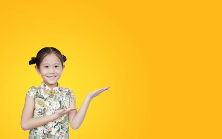Beautiful Asian little girl wearing cheongsam with smiling and welcome gesture celebrating for happy Chinese New Year isolated over yellow background with copy space.