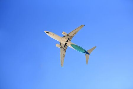Airplane flying on blue sky. Seen from below.