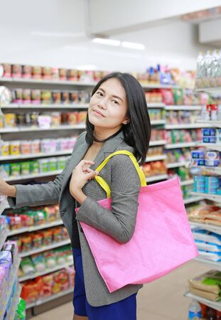 Asian woman carrying a pink recycle bag (spun ball bag) while go to supermarket. Reuse and reduce global warming concept.