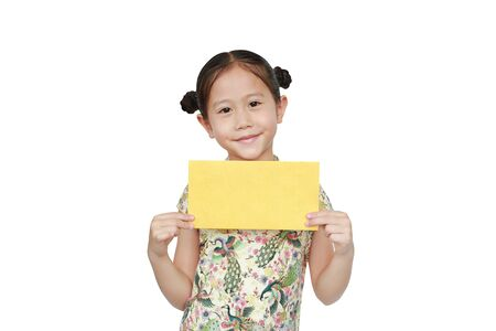 Happy Chinese New Year. Asian little girl wearing cheongsam smiling and holding gold envelope isolated on white background.