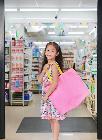 Pretty Asian little girl carrying a pink recycle bag (spun ball bag) while go to supermarket. Reuse and reduce global warming concept.
