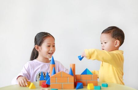 Asian little child girl and baby boy playing a colorful wood block toy on table over white background. Sister and her brother playing together. Фото со стока