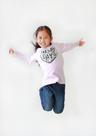 Smiling little Asian child girl freedom movement jumping in air over white background. Фото со стока