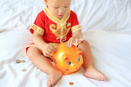 Close up little Asian baby boy in traditional Chinese dress putting some coins into a piggy bank sitting on bed at home. Kid saving money concept. Focus at piggybank.