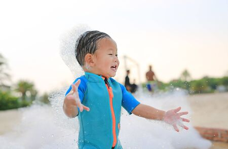 Happy and fun of little asian baby boy in swimming suit having fun in foam party at the pool outdoor.