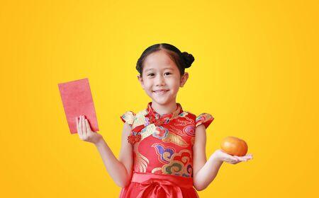 Niña bonita asiática vistiendo cheongsam rojo tradicional sosteniendo un sobre rojo rojo y fruta naranja en manos aisladas sobre fondo amarillo. Celebración del año nuevo chino. Foto de archivo