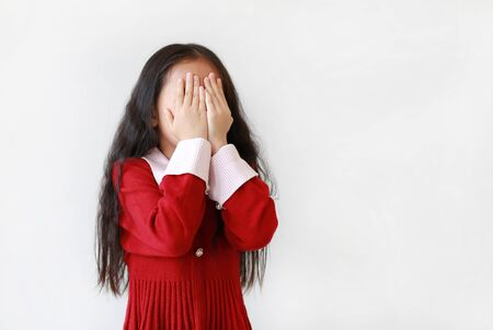 Portrait of little Asian child girl covering eyes with hands isolated over white background with copy space.