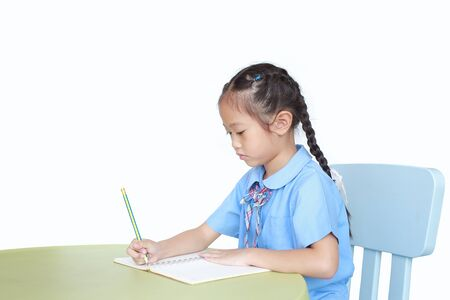 Intend little kid girl in school uniform writing on notebook at desk isolated over white background.