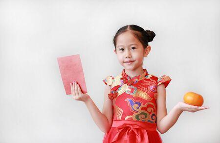 Hermosa niña asiática vistiendo cheongsam rojo tradicional sosteniendo un sobre rojo rojo y fruta naranja en manos aisladas sobre fondo blanco. Concepto de celebración del año nuevo chino. Foto de archivo