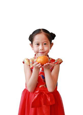Niña asiática en cheongsam rojo tradicional sosteniendo una fruta naranja en manos aisladas sobre fondo blanco. Concepto de celebración del año nuevo chino. Foto de archivo