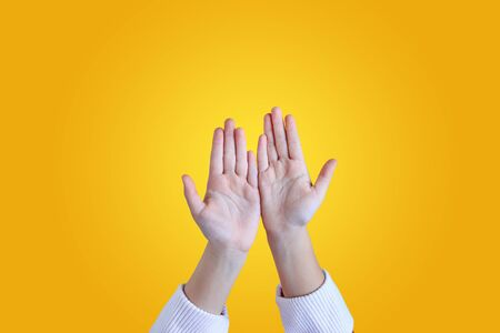Close up kid hands gesture open palm isolated on yellow background. Фото со стока