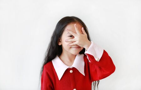 Cheerful Asian little girl covering her eyes by hand over white background.